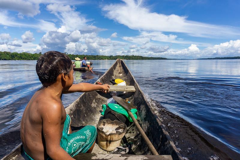Kleber Sanches sentado na proa da canoa no Rio Negro no caminho para uma viagem para o Rio Curicuriari. Foto: Karolin Obert, 2017.