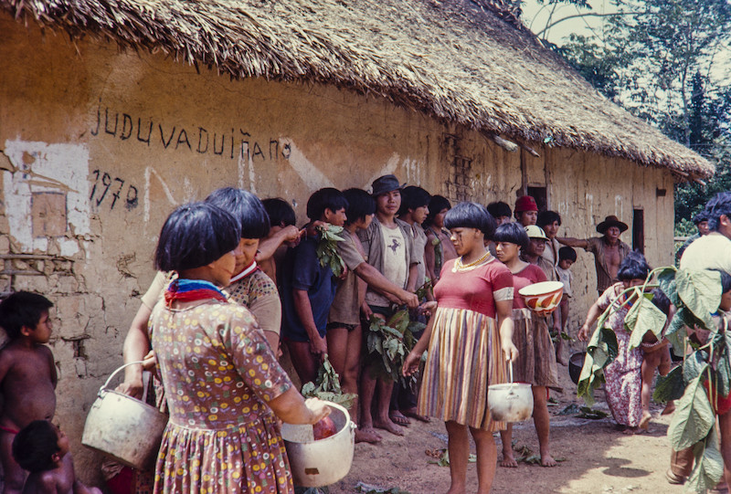 Mulheres distribuem chibé armazenados em panelas de alumínio e servidos em cuias. Fuduuwaadunnha. TI Yanomami, Roraima. Alcida Ramos, 1974.