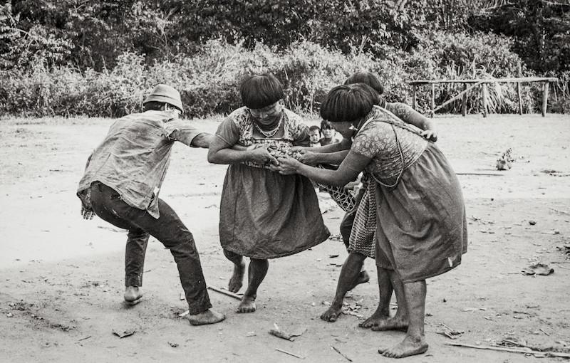 Caçador, ao chegar na aldeia com a caça, duela com as mulheres que correm para arrancar o embrulho (''maji'') de sua mão. Fuduuwaadunnha. TI Yanomami, Roraima. Ana Gita de Oliveira, 1974.